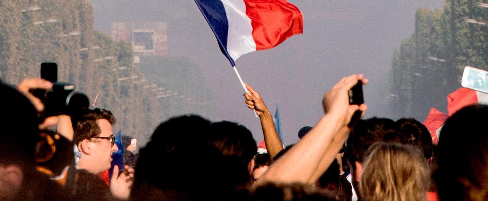 Persona sosteniendo la bandera de Francia durante las protestas.