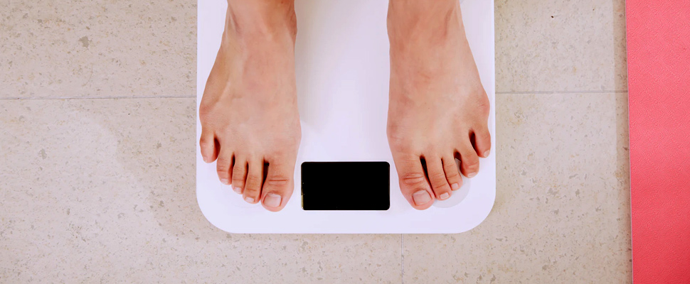 Person standing on digital bathroom scale.
