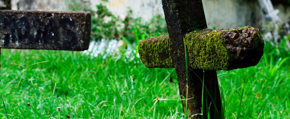 Cruz de concreto enterrada en un cementerio.
