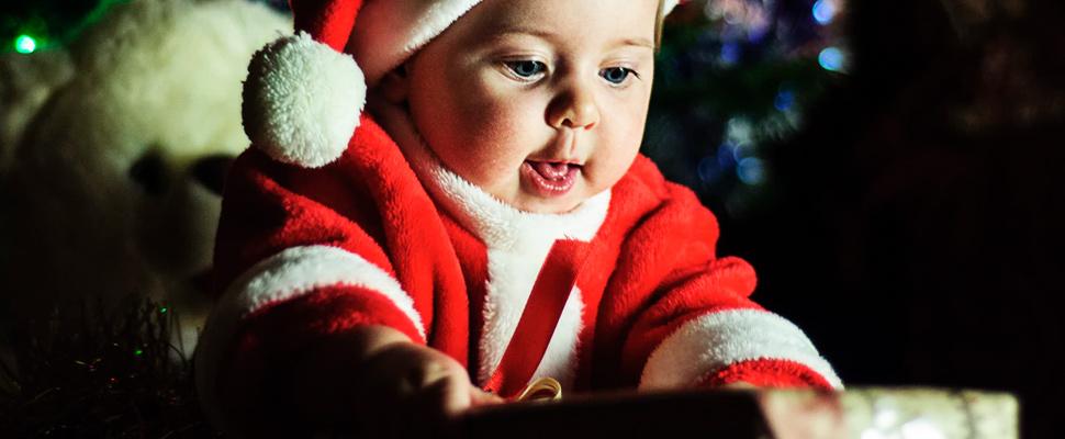 Bebé con traje de Santa Claus desenvolviendo un regalo.