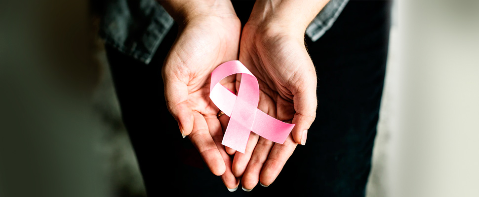 Woman holding a ribbon of the fight against cancer.