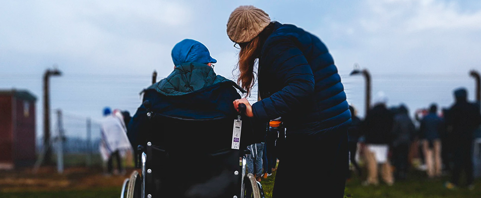 Woman standing near person in wheelchair.