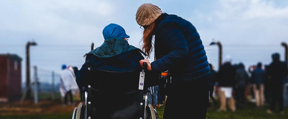 Mujer de pie junto a la persona en silla de ruedas.
