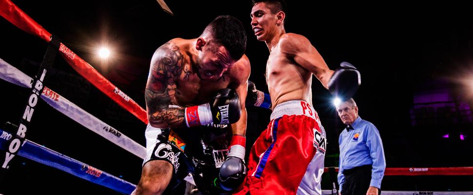 Dos hombres peleando en el ring de boxeo.
