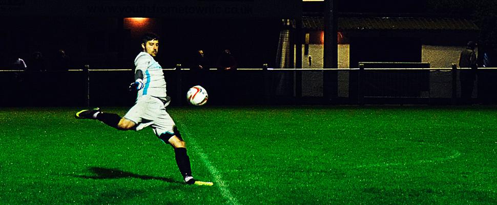 Futbolista pateando un balón dentro del campo de juego.