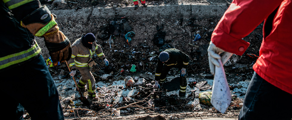Rescue workers search the scene, where a Ukrainian airplane carrying 176 people crashed.