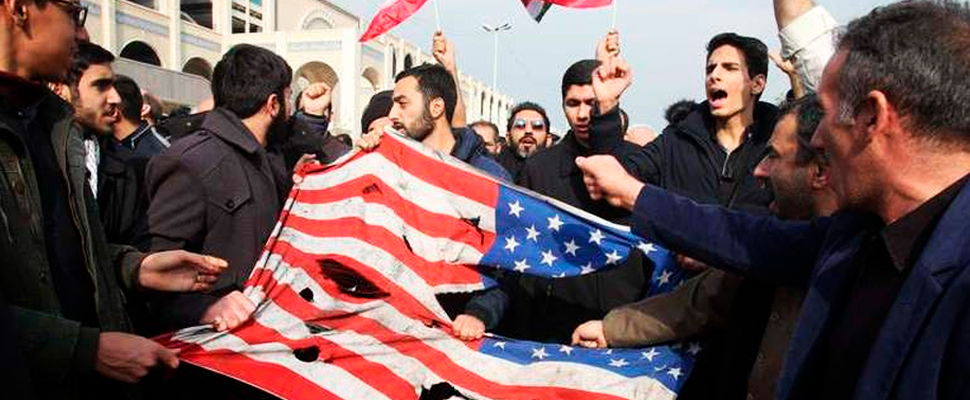 Manifestantes iraníes con una bandera de Estados Unidos.