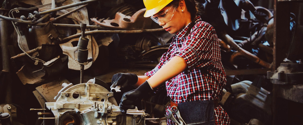 Woman engineer checking parts of a vehicle.