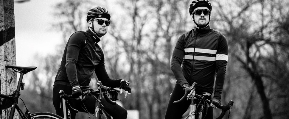 Grayscale photography of two men cycling during daytime.