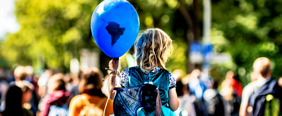 Girl holding a balloon with map drawn into it.