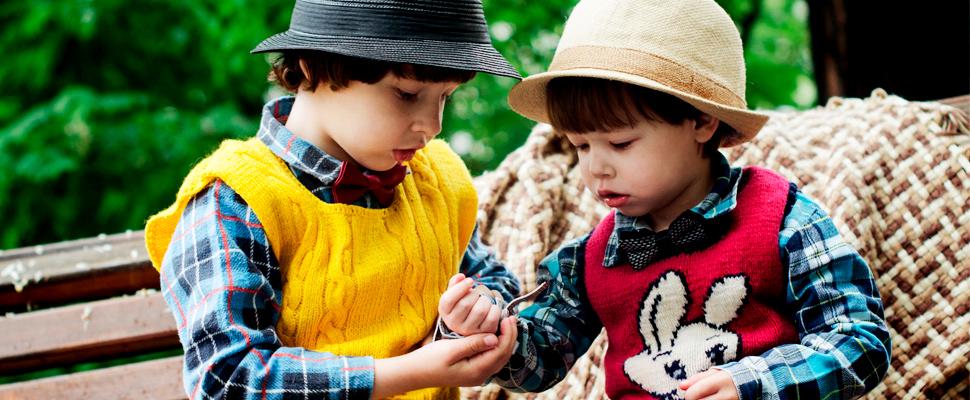 Dos niños sentados en un banco.