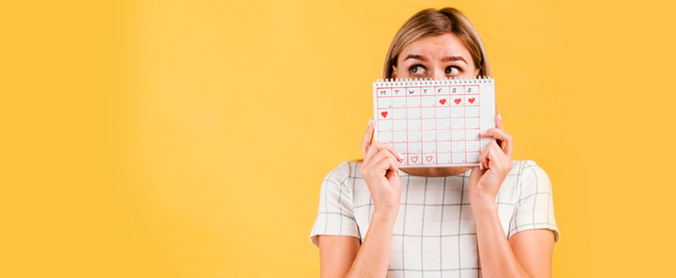 Woman holding a calendar with marked menstrual cycle days.