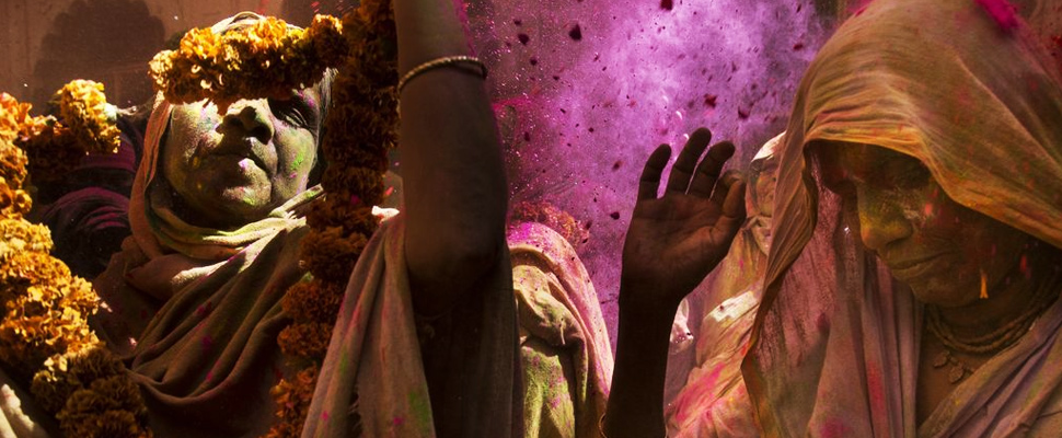 Women participate in the Holi ceremony at the Gopinath Temple in India