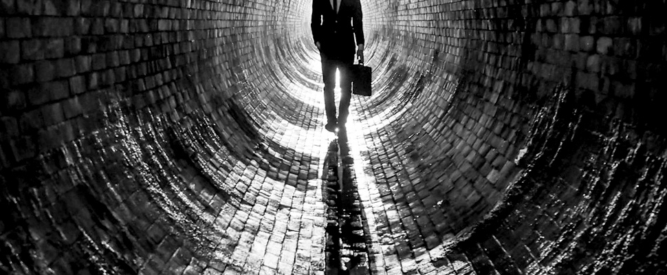 Man walking inside a tunnel.