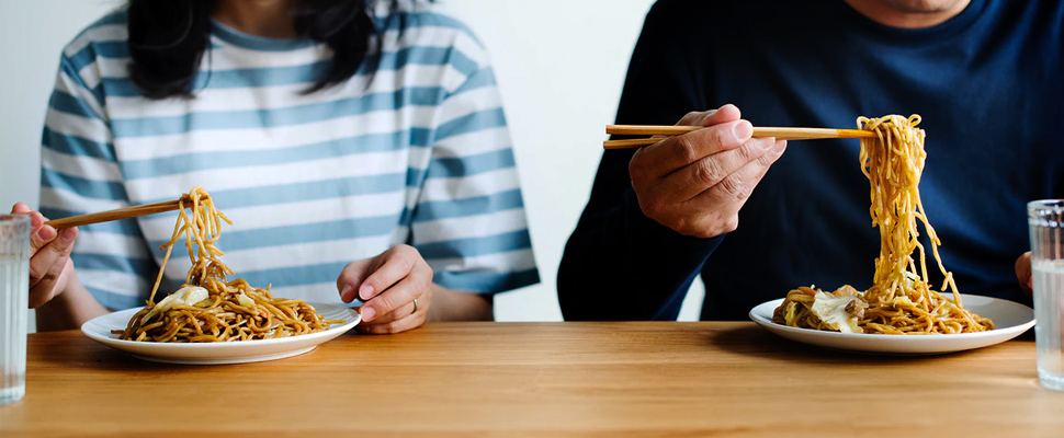 Couple eating spaghetti.