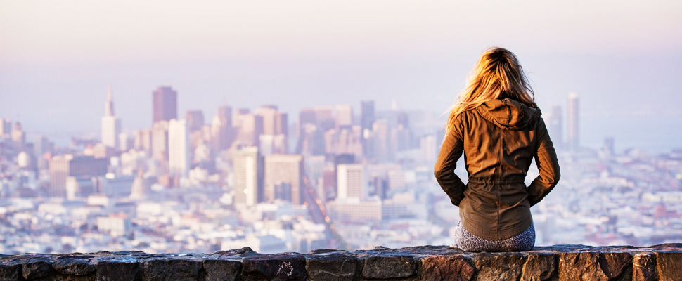 Woman on rock platform viewing the city architecture.