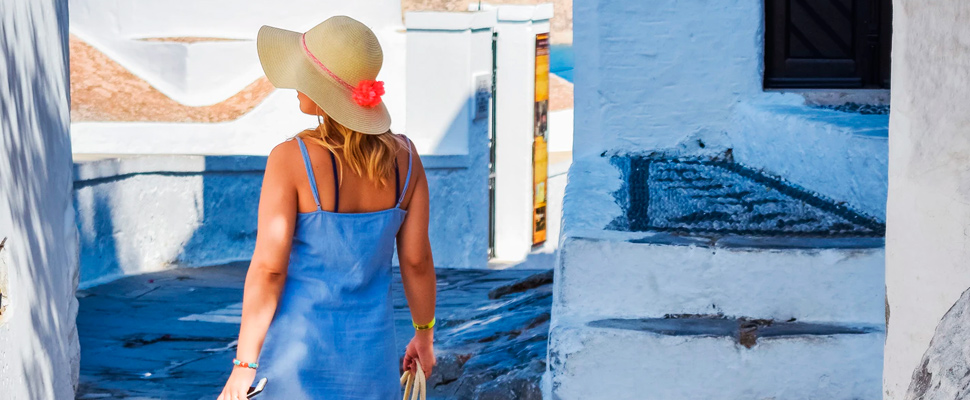 Woman wearing blue dress and hat.