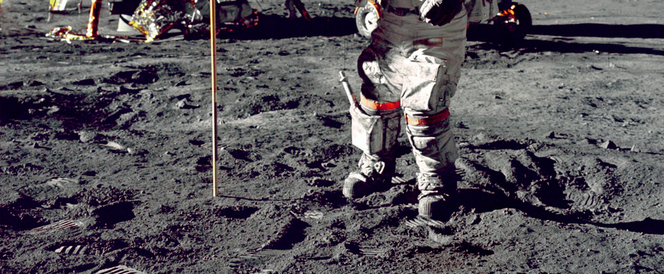 Astronaut standing on moon beside the USA flag.