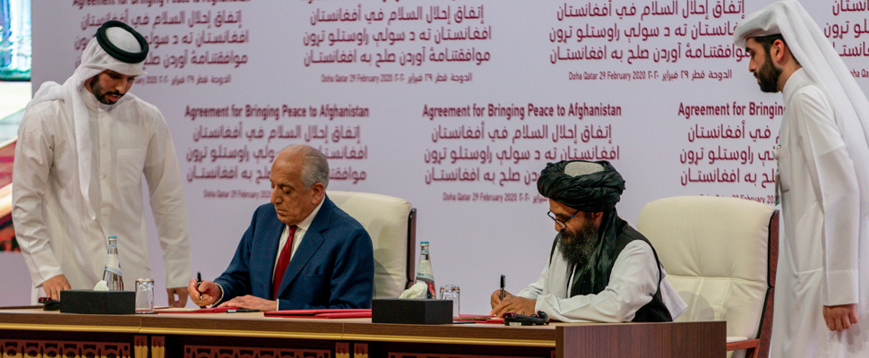 United States representative Zalmay Khalilzad and Taliban leader Mullah Abdul Ghani Baradar signing agreement.