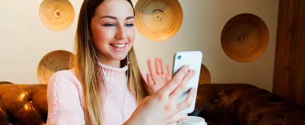 Girl holding her cell phone making a video call.