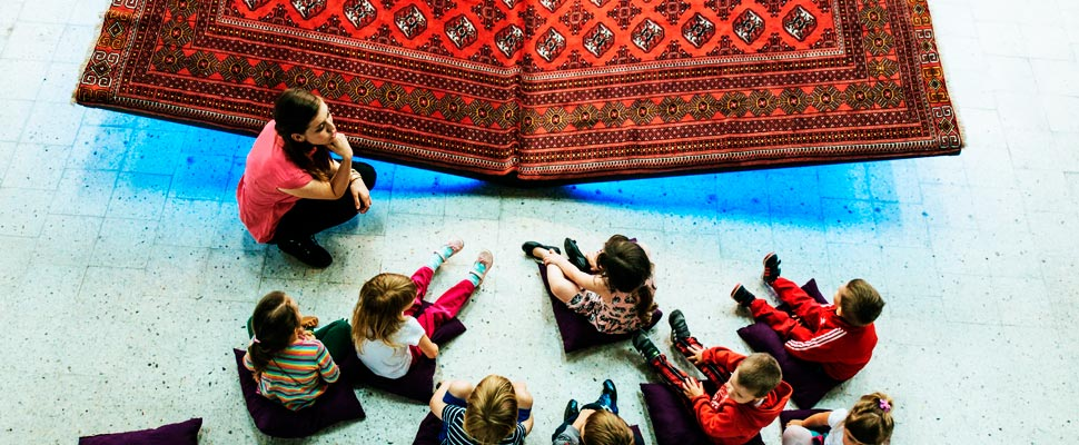 Children and woman sitting on floor in the museum.