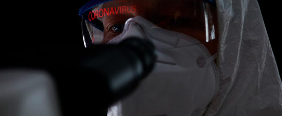 Man wearing a biological protection suit looking through a microscope.
