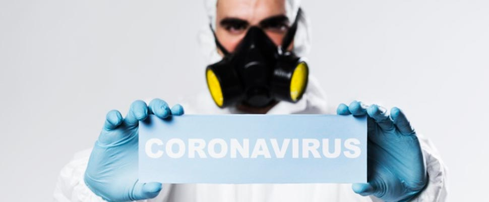 Man in a biological suit holding a sign that says 'Coronavirus'.
