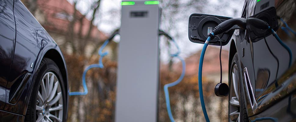 Two electric cars are charged at a charging station.
