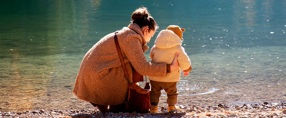Mother and child near lake.