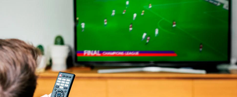 Man watching a soccer game on his television.