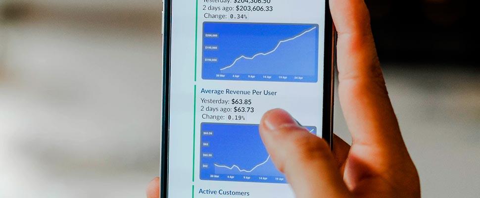 Persona con teléfono inteligente mostrando datos de valores.