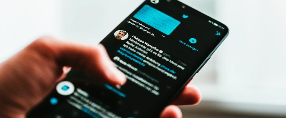 Persona con smartphone con aplicación de Twitter.
