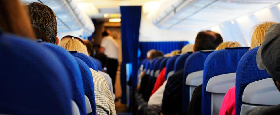 Personas sentadas dentro de un avión.