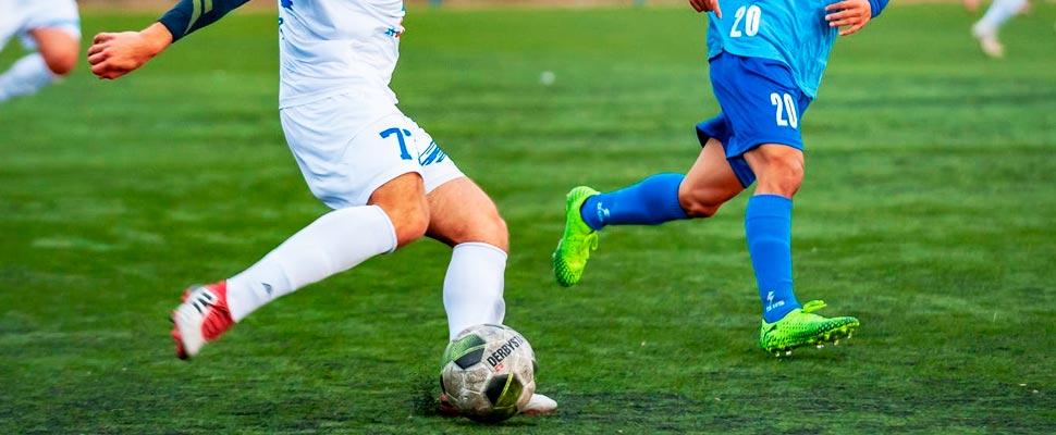 Dos hombres jugando fútbol.