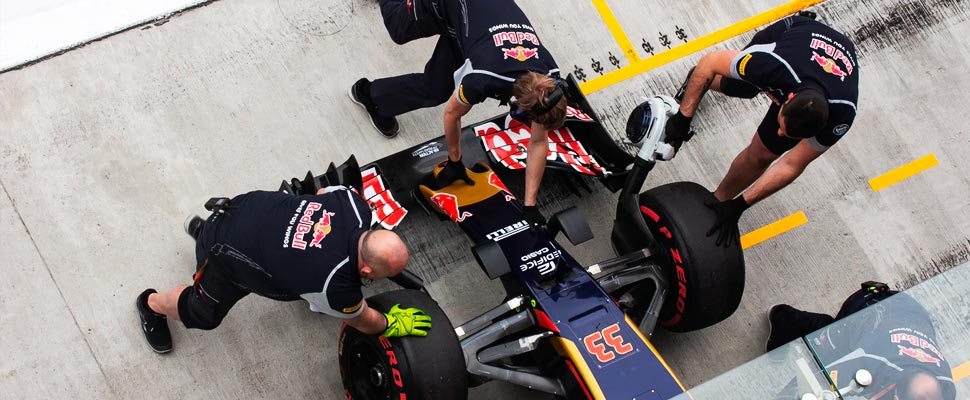 Three men at a pit stop in Formula 1.