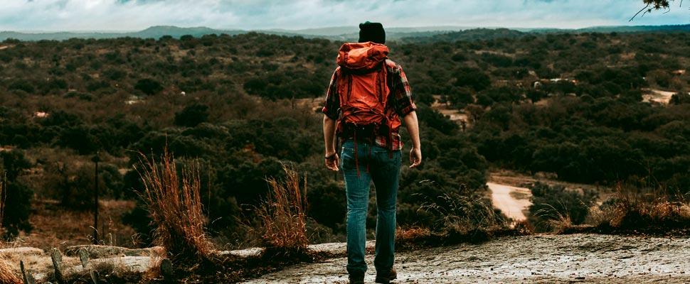 Mujer de pie en un sendero de área natural.