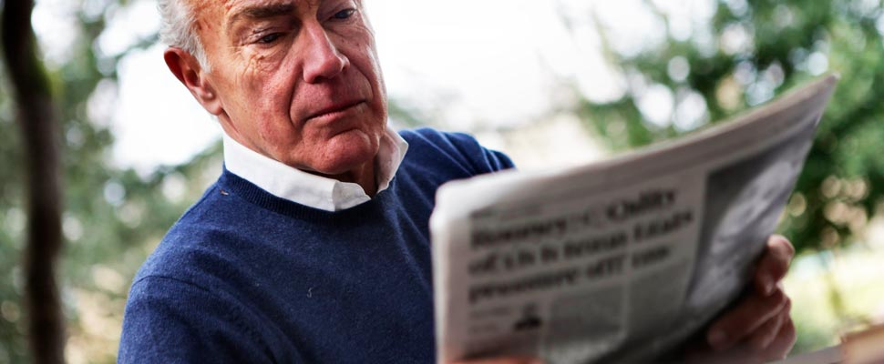 Man in blue sweater reading newspaper
