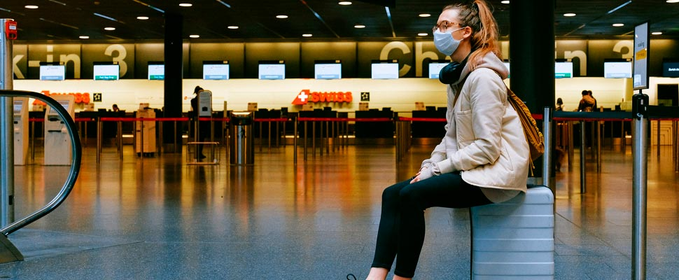 Woman wearing a face mask sitting on her travel suitcase at an airport.