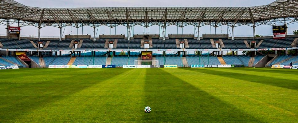 Balón de fútbol en medio de un estadio vacío.