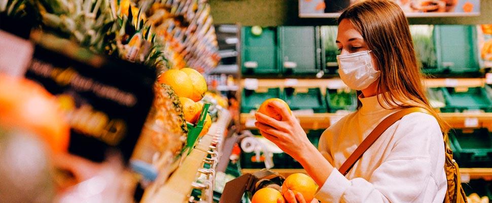 Mujer con máscara en el supermercado.