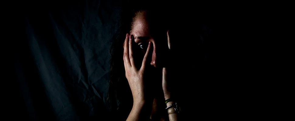 Mujer sosteniendo su rostro en cuarto oscuro.