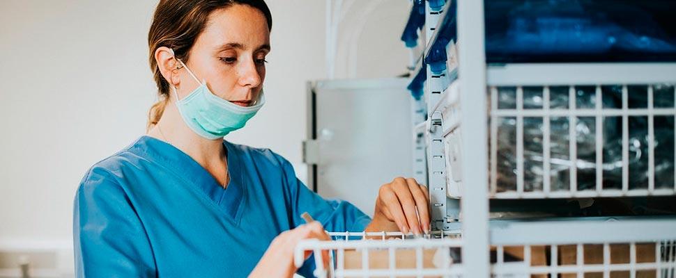 Enfermera buscando medicamentos en una giveta.