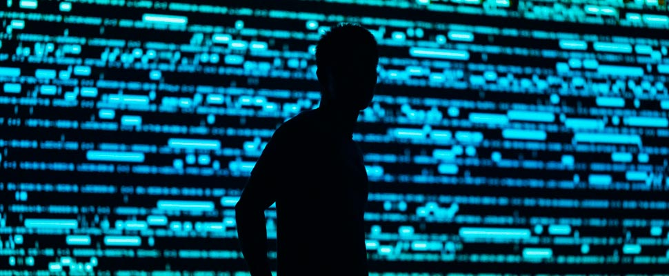 Silhouette of a man on a background of computer codes.