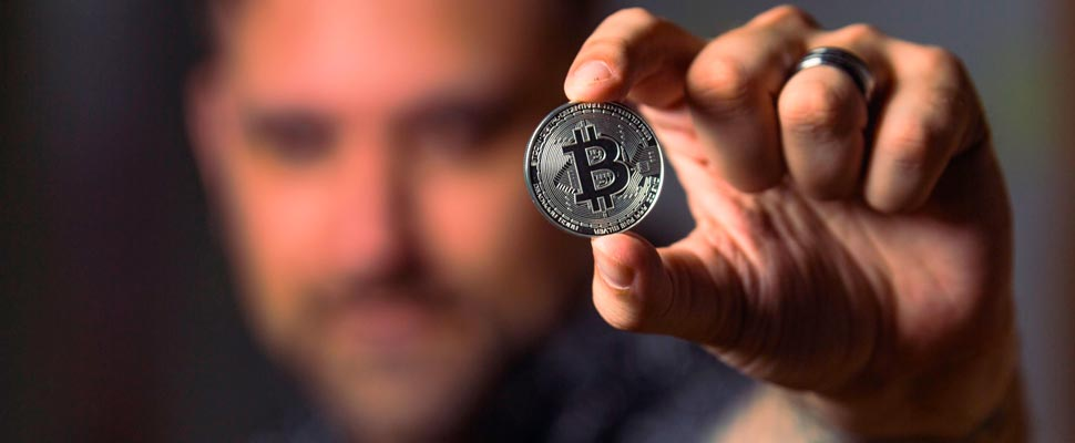 Man holding a bitcoin coin.