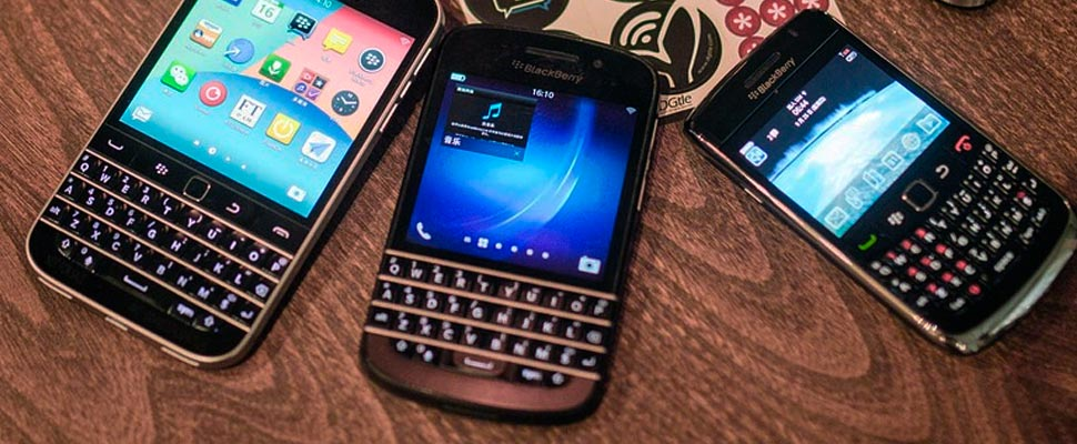 Three cell phones of the 'BlackBerry' brand.