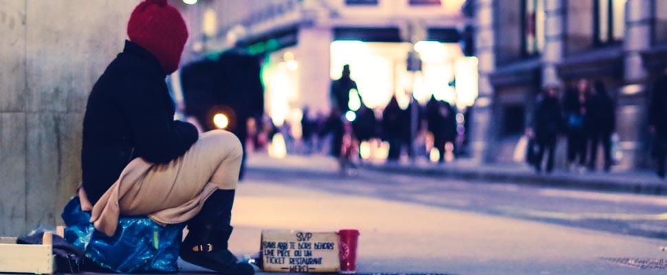 Persona sentada en la calle.