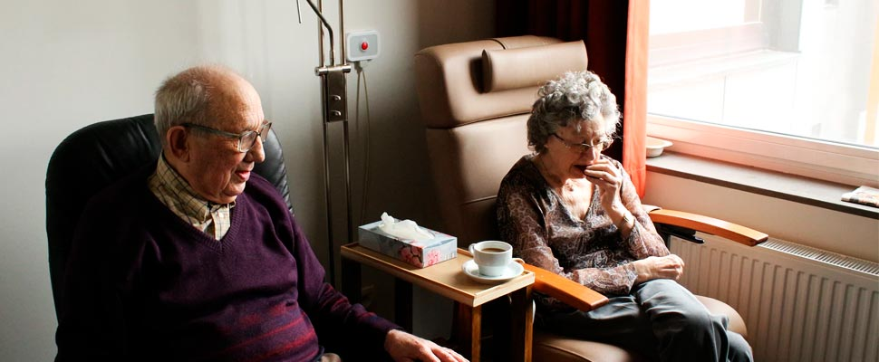 Couple sitting side by side at a nursing home.