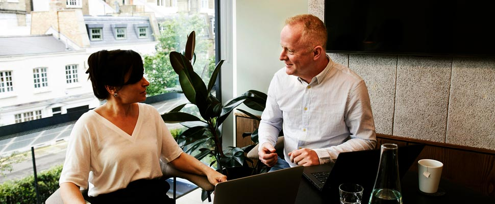 Hombre y mujer converasndo en una oficina.