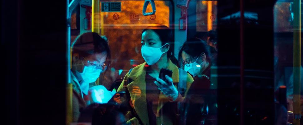 Personas dentro de un autobús con máscaras