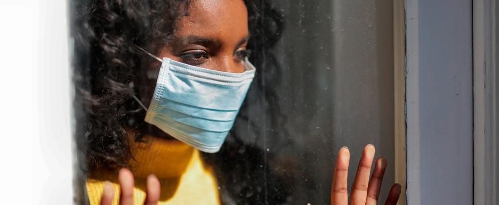 Mujer joven mirando por una ventana con una máscara